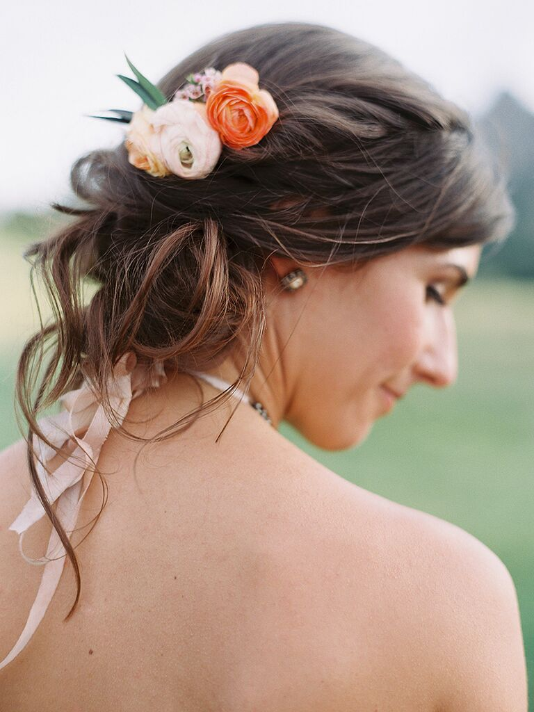 Bridesmaid updo idea for a strapless dress with a couple fresh blooms
