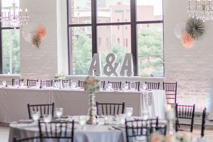 The couple were sold on the modern, clean space at Loft 310 for their reception. Amber designed the tables, and her mother helped to make the silk-flower pomanders that topped some of the silver candlesticks.