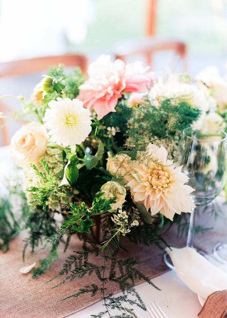 Burlap linens gave way to cascading arrangements of cafe au lait dahlias, waxflowers, ferns, roses and ranunculus, their romantic appeal adding softness to the otherwise rustic decor.