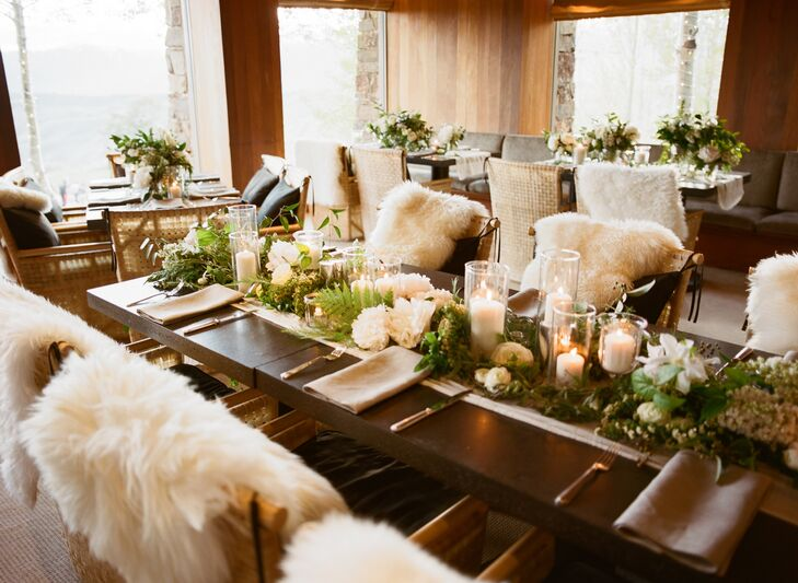 Rustic stone tables were pushed together to form one long table in the middle of the reception hall with green garlands running down the middle. Each table was decorated with candles, florals, and faux sheepskin placed on the backs of the seating.