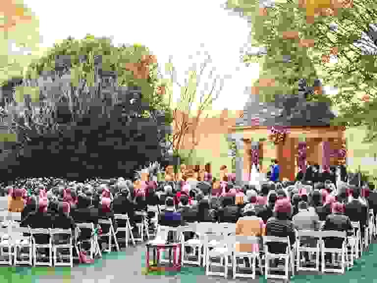 Outdoor wedding ceremony under rustic gazebo