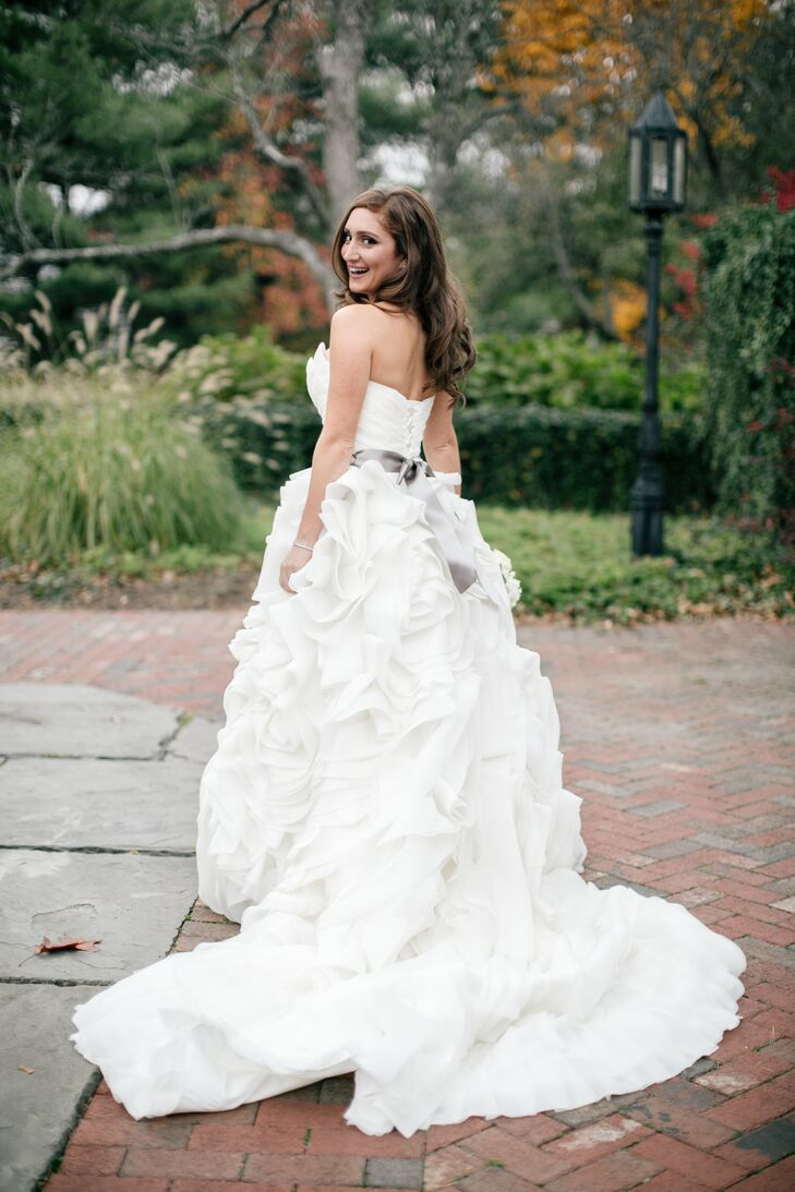 Joelle looked radiant in a Maggie Sottero ball gown, which she bought at Bijou Bridal. The dress features a voluminous, ruffled train. Joelle also wore a satin gray sash.
