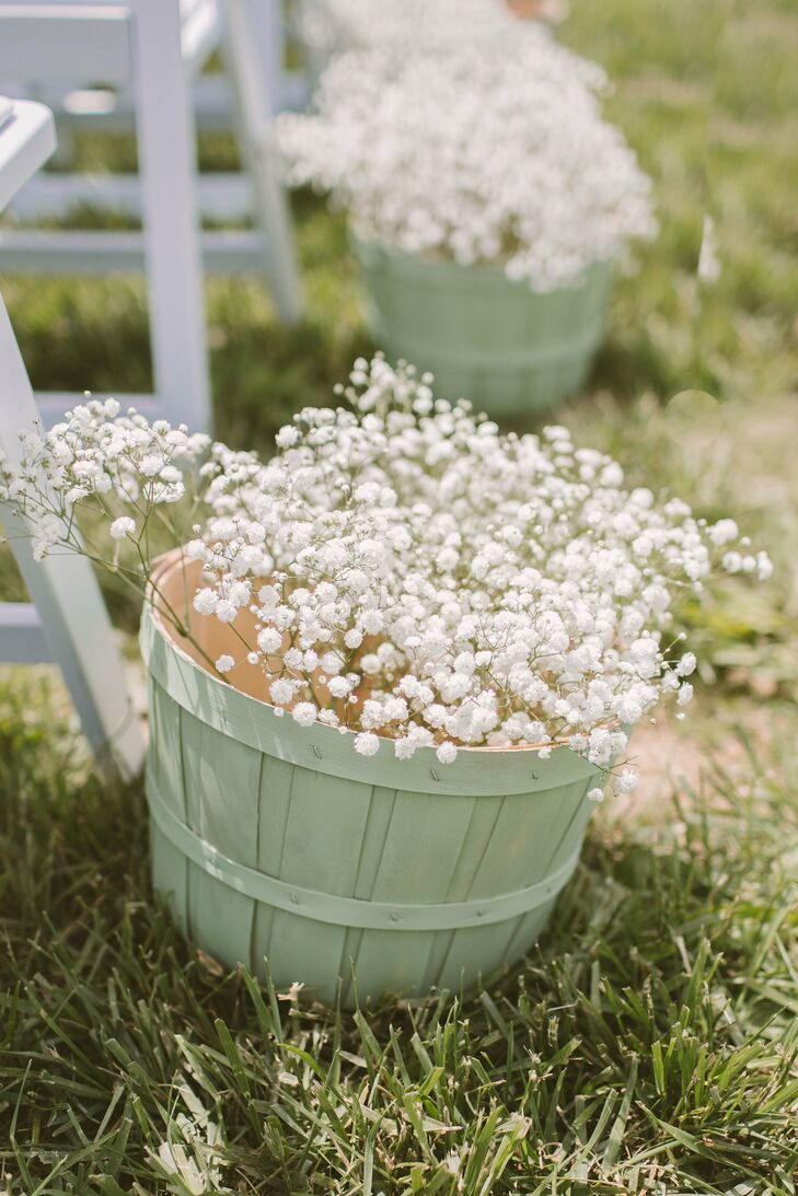 Hand-painted baskets filled with baby's breath lined the aisles of the outdoor ceremony.