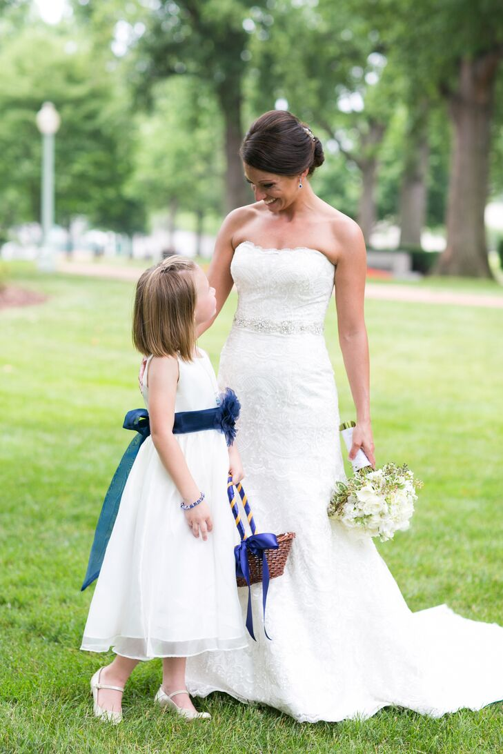 Their navy and gold colors were not lost on the flower girl's look. Her white tea-length chiffon dress was accented with a bold blue feather flower at the center. Her basket even had navy and gold ribbon wrapped around the handle as a subtle tribute to the US Naval Academy.