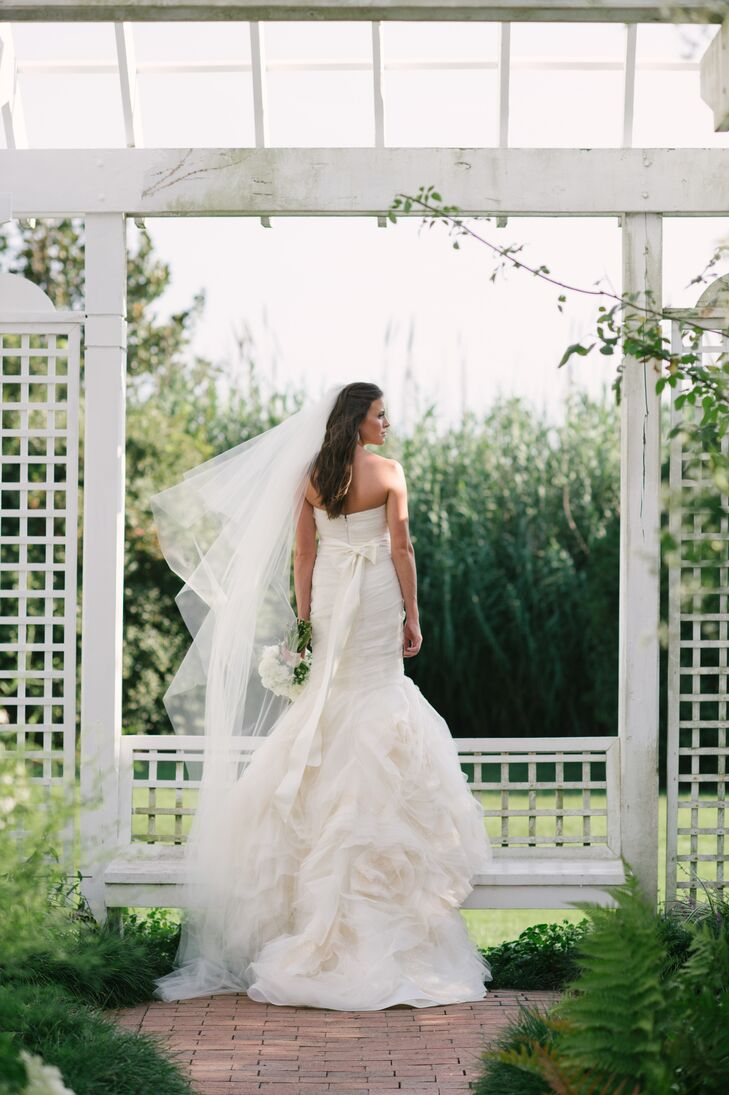 """My dress was very soft and whimsical, almost ethereal, with lots of tulle and a beautiful organic layering at the bottom,"" says Casey. ""The long train was my favorite part of my wedding day ensemble— it looked so beautiful from behind!"""
