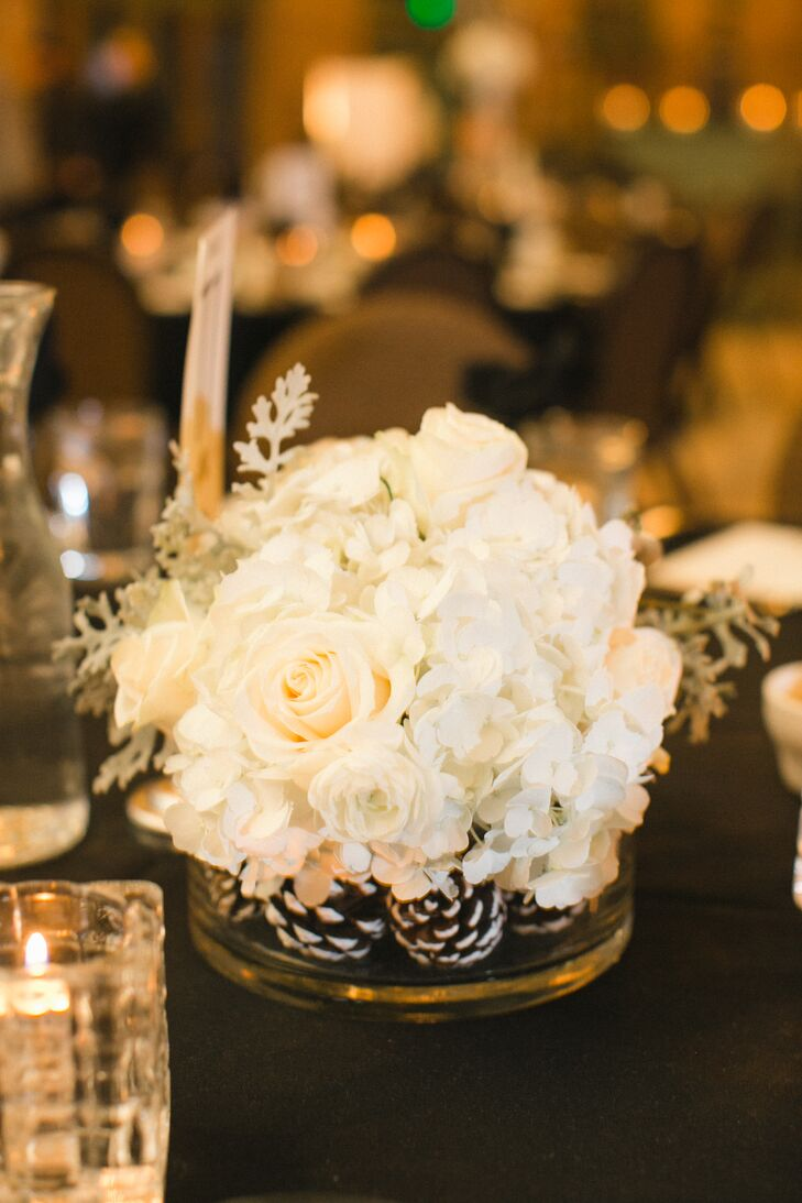 Amy and Matthew had the florists at Studio B Floral create three different styles for their centerpieces to keep the decor feeling fresh and unique. The tall centerpieces were arranged in hurricane vases and filled with ivory hydrangeas, pinecones and shimmery silver branches. There were also bunches of pinecones, roses and dusty miller arranged in small round vases and clusters of four square vases boasting pinecones or cream-colored roses and candles.
