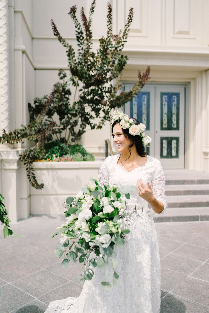 Kourtney's lacy dress had a mix of floral patterns, which fit well with the day's tropical theme. She paired her gown with a white rose flower crown, and a luscious bouquet of eucalyptus and white blossoms created by White Lily Lane.