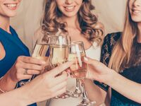 Bride with friends at bridal shower holding champagne