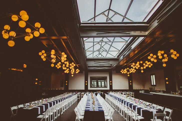 Long rectangle tables were draped with navy tablecloths and surrounded by white chairs, complementing the modern reception space.