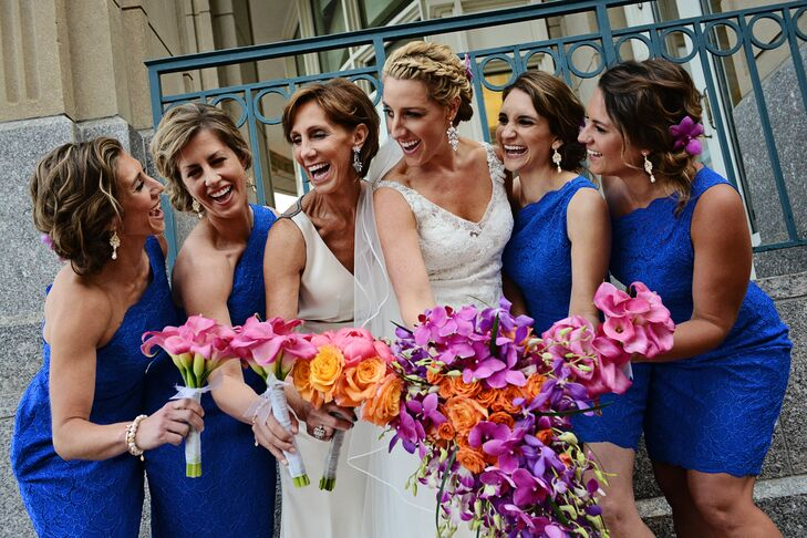 When it came to her bridesmaids' attire, Ashley decided to have the girls don matching styles to create a cohesive look. She selected a cocktail-length dress with a flattering one-shoulder neckline, lace overlay and vibrant blue fabric, which made their bright pink and orange bouquets really pop.