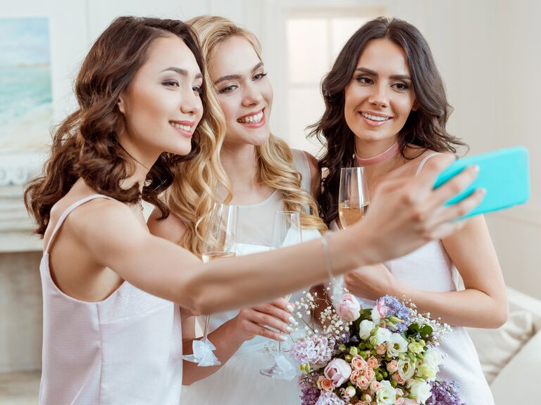 Bride and bridesmaids taking selfie on wedding day