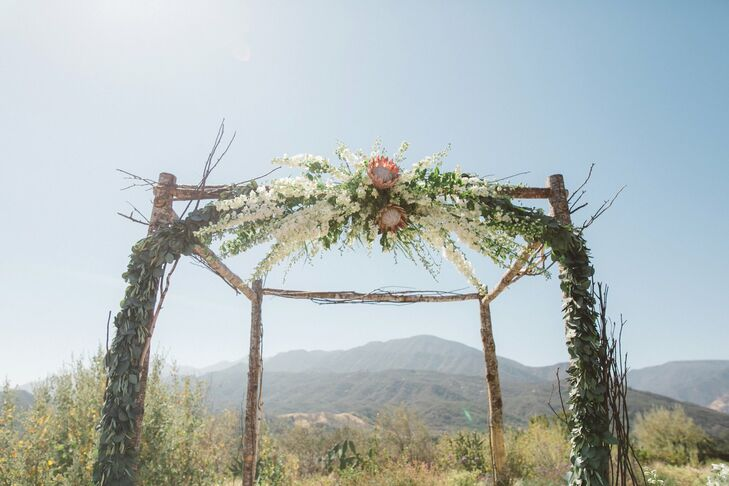 Tracy and Michael exchanged vows under a handcrafted birch-wood arch at Red Tail Ranch in Ojai, California. Two of the arch's four legs were wrapped with eucalyptus, and the front was topped with a white and blush pink floral garland.