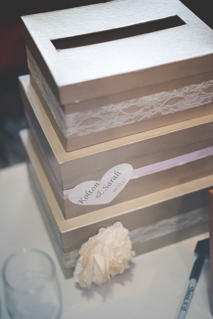 Stacks of brown boxes wrapped with peach and pink ribbon served as the card box for wedding gifts.
