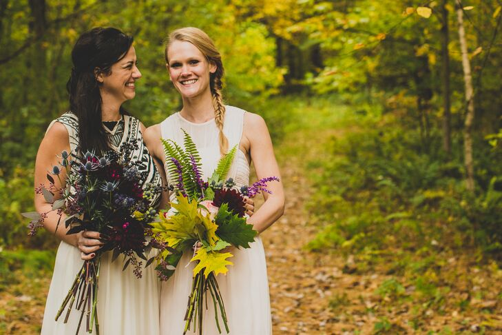 The bride stood next to her maid of honor, who wore a soft blush dress from Topshop and held a bouquet of burgundy dahlias and blush flowers accented with thistle, berries, fern and leaves, created by Mt. Lebanon Floral.