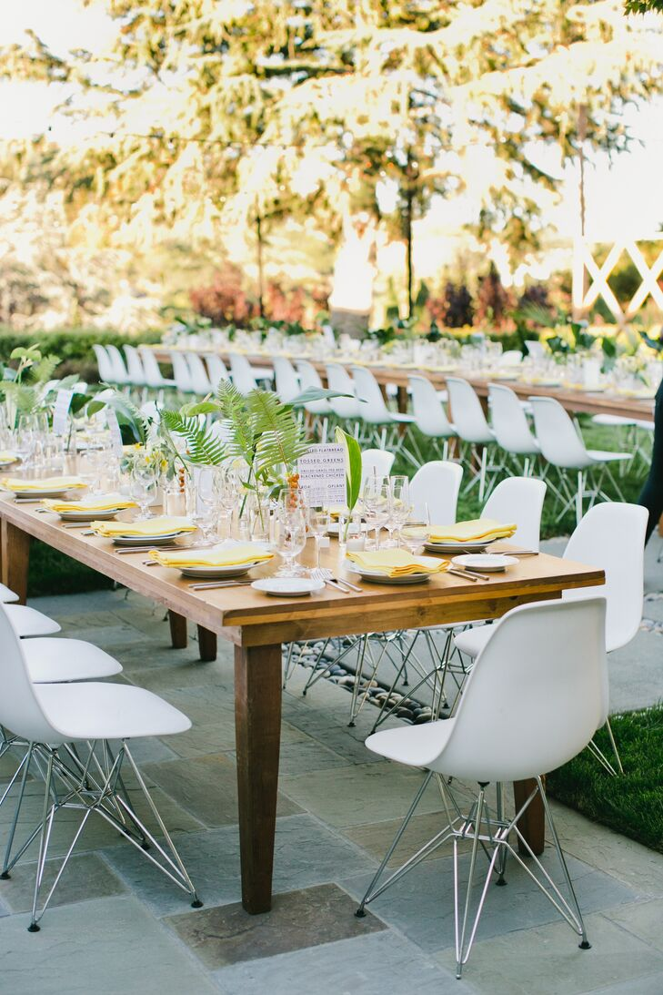 The long wooden dinner tables used white chairs from the ceremony as seating and were topped with clear vases filled with fresh ferns and greens. Yellow napkins added a pop of color.