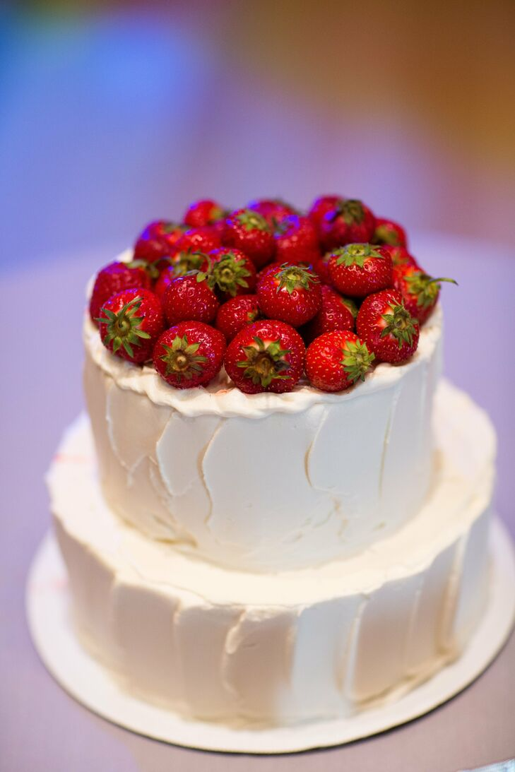 The simple two-tier cake was iced in white buttercream and topped with fresh strawberries.