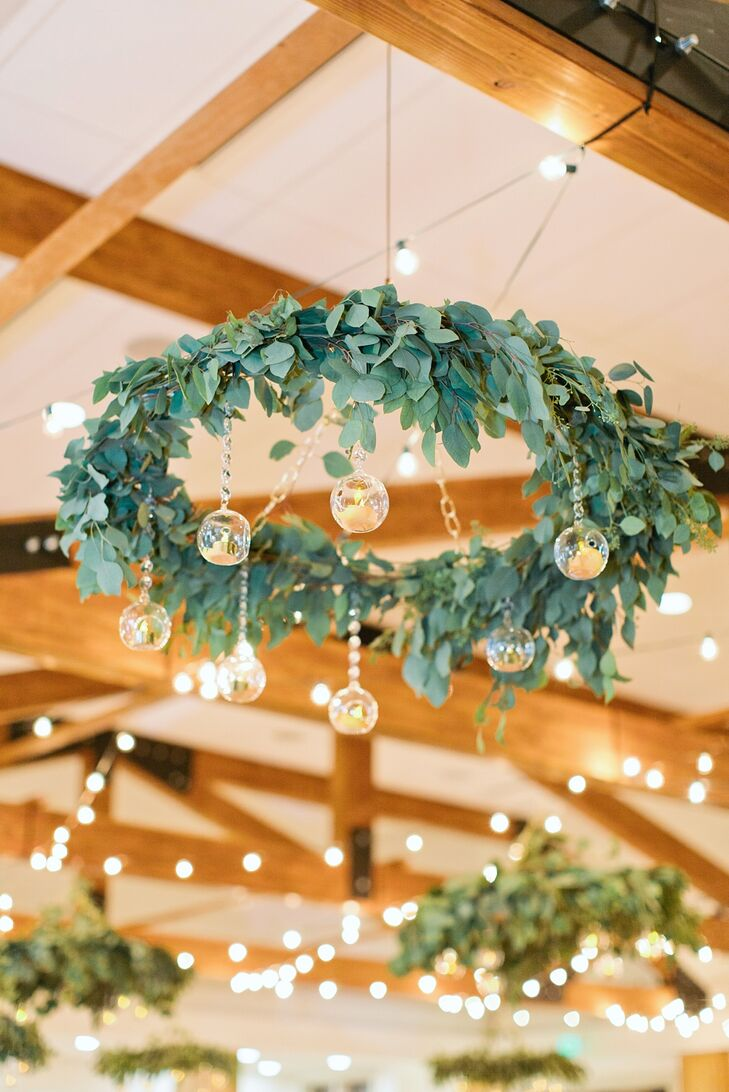 "Rustic rafters in the ceiling didn't exactly fit the garden theme, so chandeliers were incorporated to ""tone it down."" In lieu of traditional lighting, the florist created rings of leaves decorated with hanging candles. These special decorations ""made the space magical,"" Brittany says. To add another soft, romantic glow, market lights were weaved through the rafters."