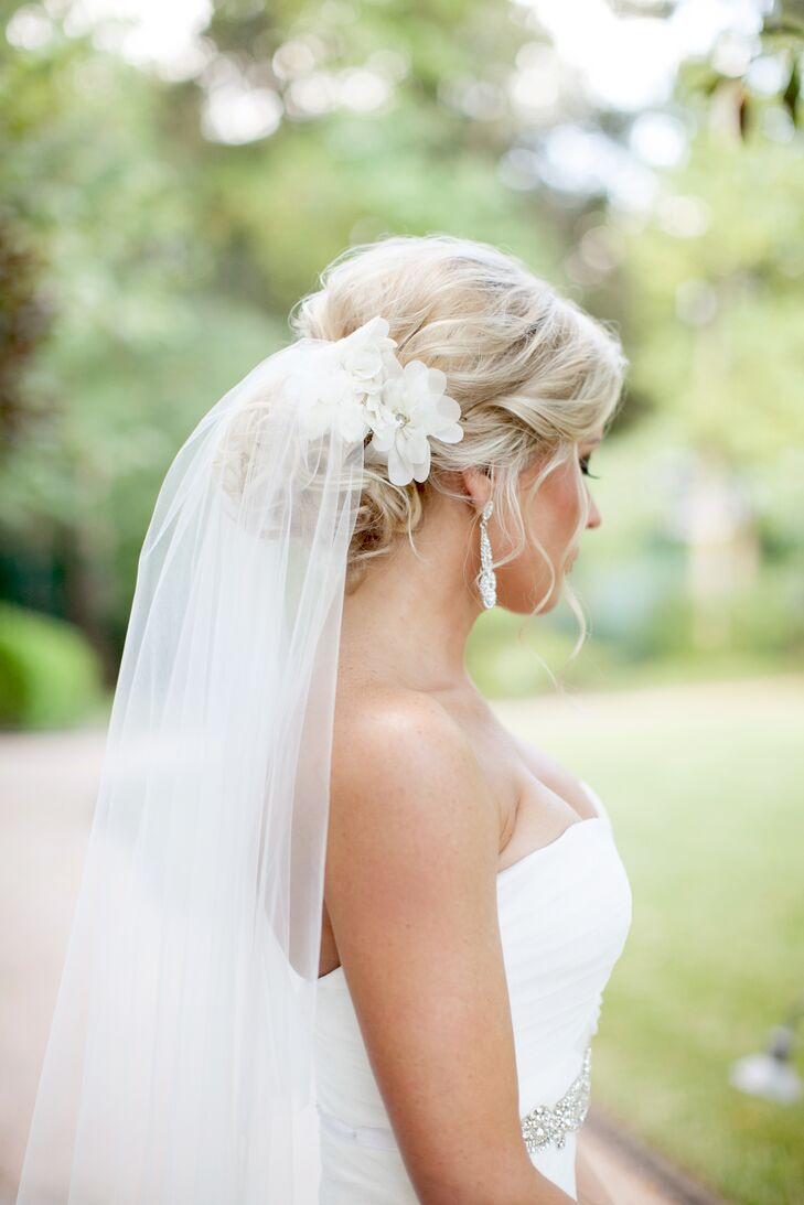Kelli wore her hair in a romantic bridal updo with a pair of white fabric flowers on the side. She also wore a sheer short veil and crystal chandelier earrings.