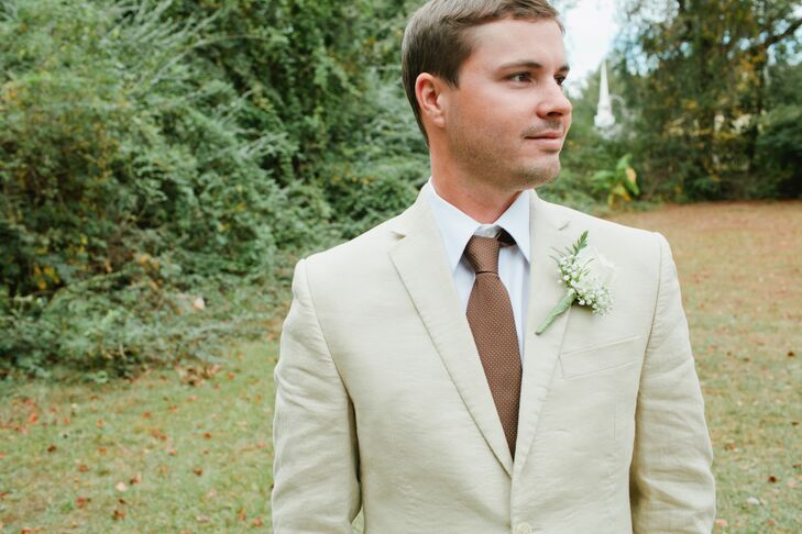 The groom wore a casual tan linen tux with a mauve tie and a baby's-breath boutonniere to complement the bride's lace gown with a champagne-colored underlay and mauve belt, as well as her cotton and baby's-breath bouquet.