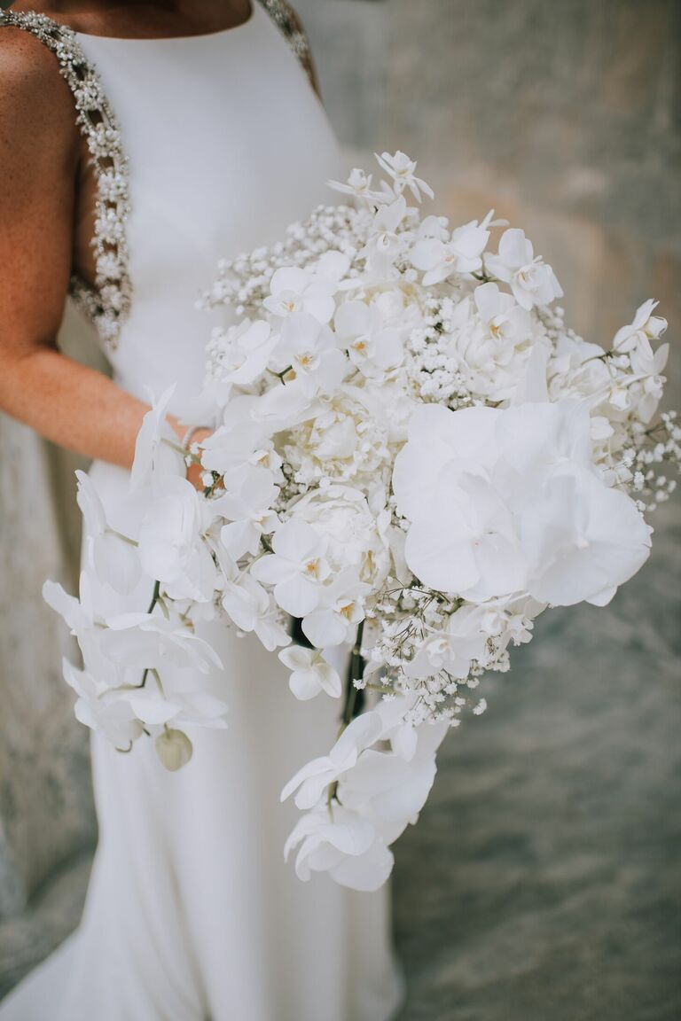 Cascading white wedding bouquet with orchids and baby's breath