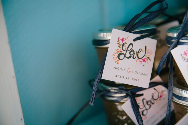 "Nicole and Coleman filled an old hutch with different flavors of homemade jams and jellies for their wedding favors. Each jar had a colorful ""love"" tag tied with a navy ribbon."