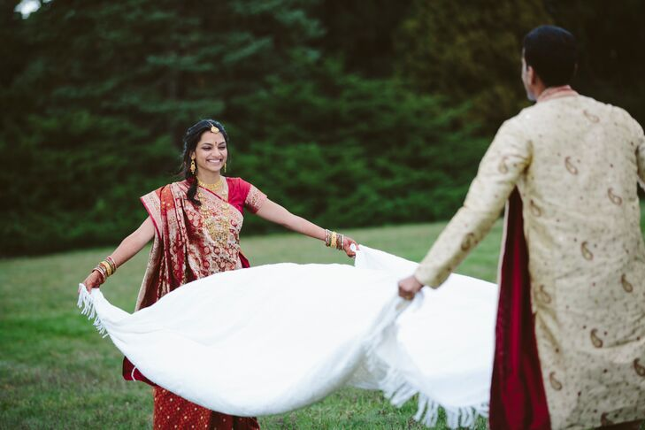 Bride and Groom Work Together To Spread White Blanket on Grass