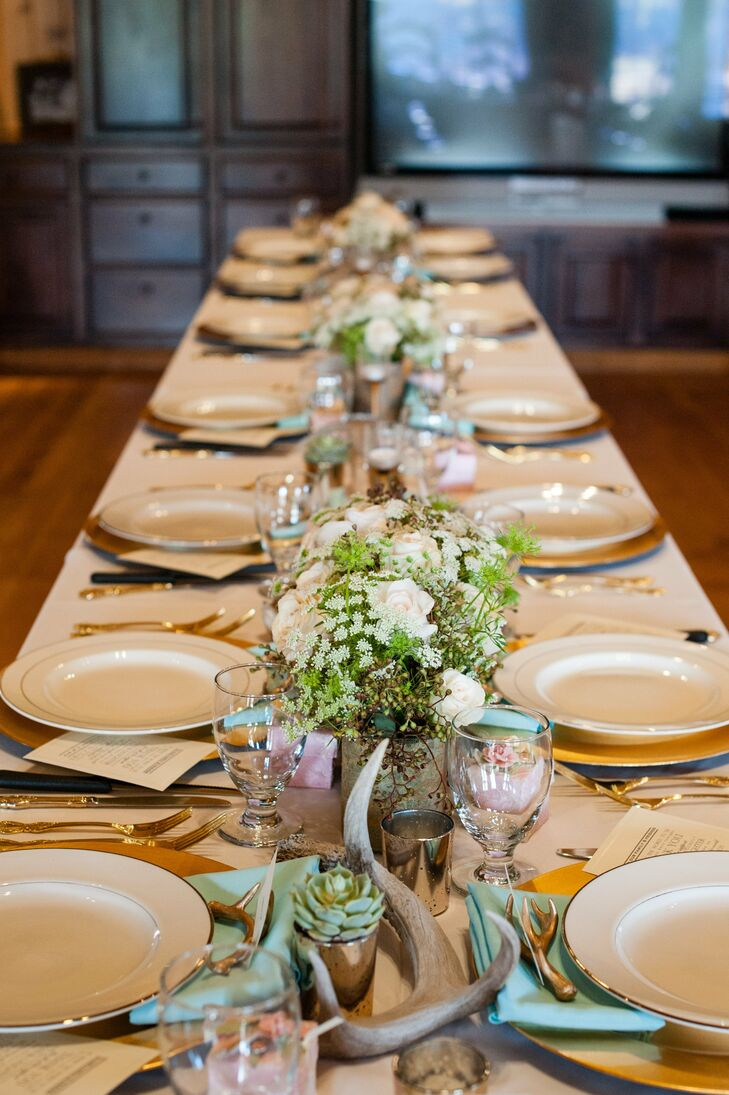 Antlers mixed with romantic white and green floral arrangements and potted succulents on each reception table.