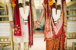 Indian Bride and Groom Hold Hands in Wedding Attire