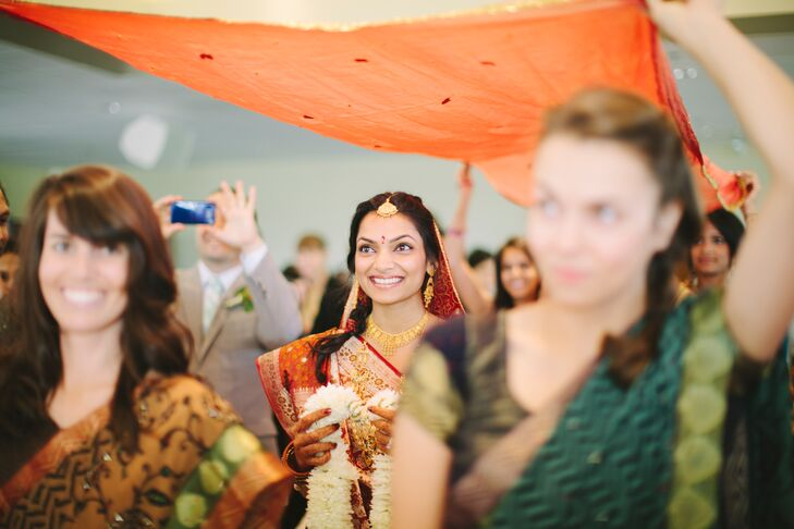 The bride glows under an orange canopy as she processes down the isle. She carries a floral necklace to be worn later on in the ceremony.