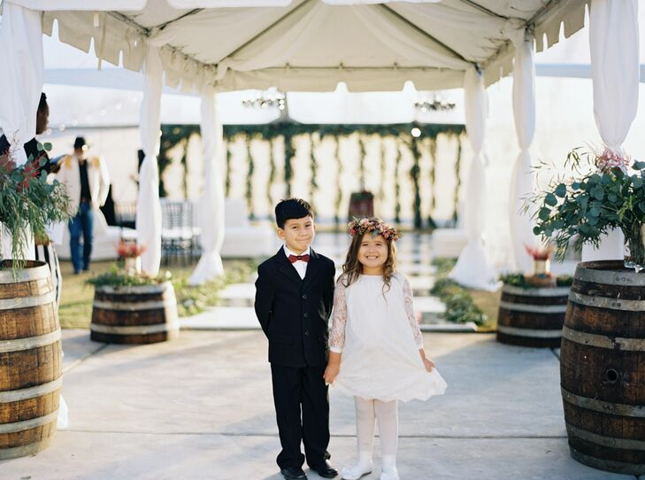 """The flower girls were dressed in white solid dresses with lace long sleeves,"" Danika says. ""I wanted to incorporate the lace because my wedding dress had lace and the long sleeves were fitting for the month of December. The ring bearers wore little black suits and carried a wooden sign with a hook on it that says 'With this ring.' """