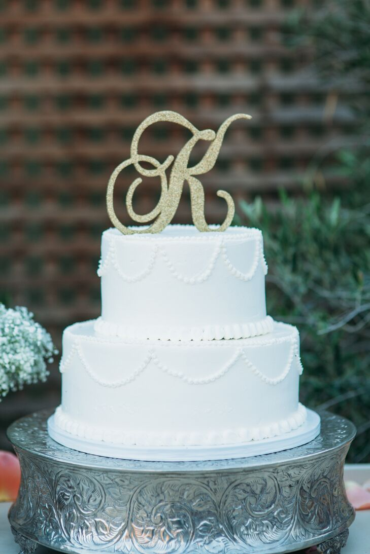 The traditional white wedding cake stood two tiers tall, with beaded icing around the bottom of each layer. The dessert had a gold topper of Monique and Shade's last-name initial, created by Solvang Bakery, which also made four other cakes served at the wedding.