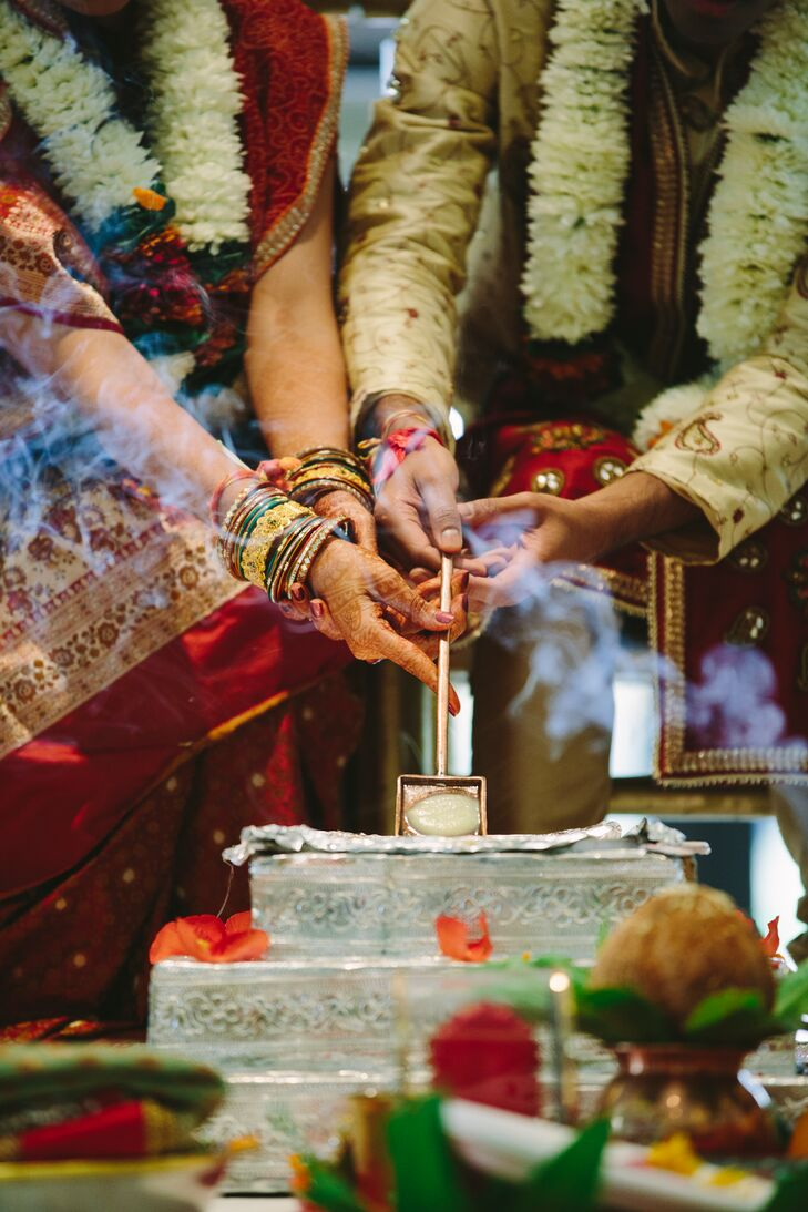 The bride and groom light incense as party of the ceremonial traditions of an Indian wedding.