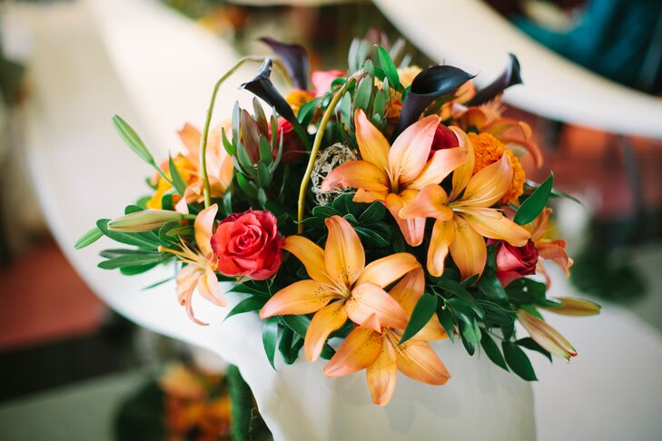 The color scheme of the wedding is seen through the bridal bouquet in the mustard yellow, green and red of the roses and calla lilies mixed with the greenery.
