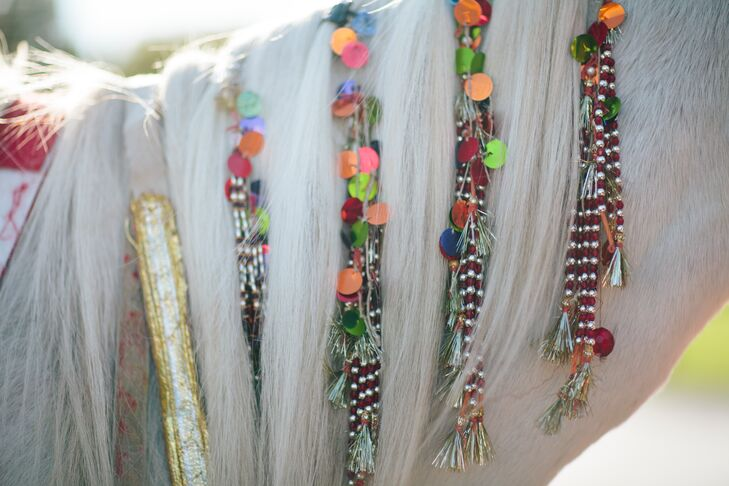 Colorful beads and sequence brighten up the soft, white hair of the horse.