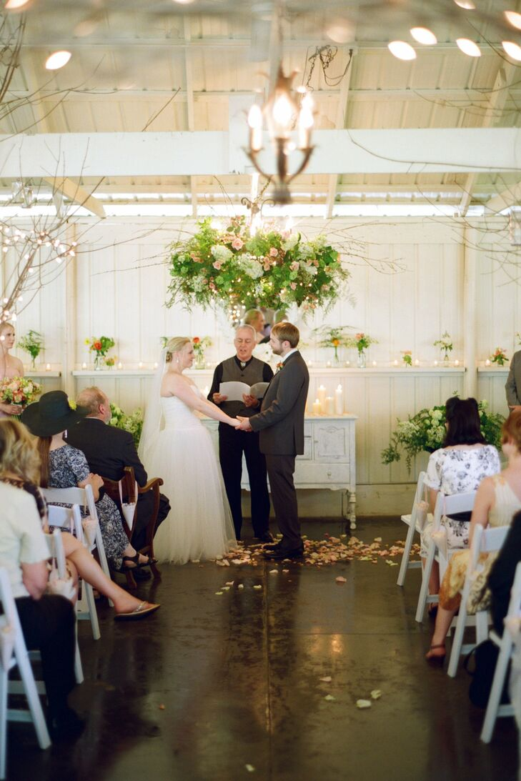 "The couple's florist, Cindie, worked her magic on the altar area, creating a flower ""chandelier"" above an old, painted wardrobe covered in flowers and candles. Pink rose petals were also scattered down the aisle and around the altar. ""It was magical,"" Zoe recalls."