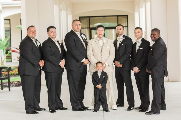 The 1920s and '30s were all about dapper, formal attire, so their wedding party suited up for the occasion. Each groomsman sported a classic black tuxedo with a neutral vest and bow tie to highlight their wedding colors. Angel stood out among them in all neutral hues and white hues. Handmade boutonnieres with white feathers and fabric flowers tied their looks together.