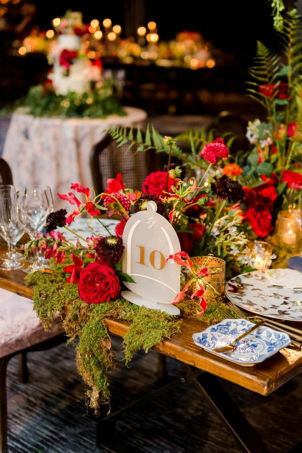 Acrylic table number surrounded by red roses and moss