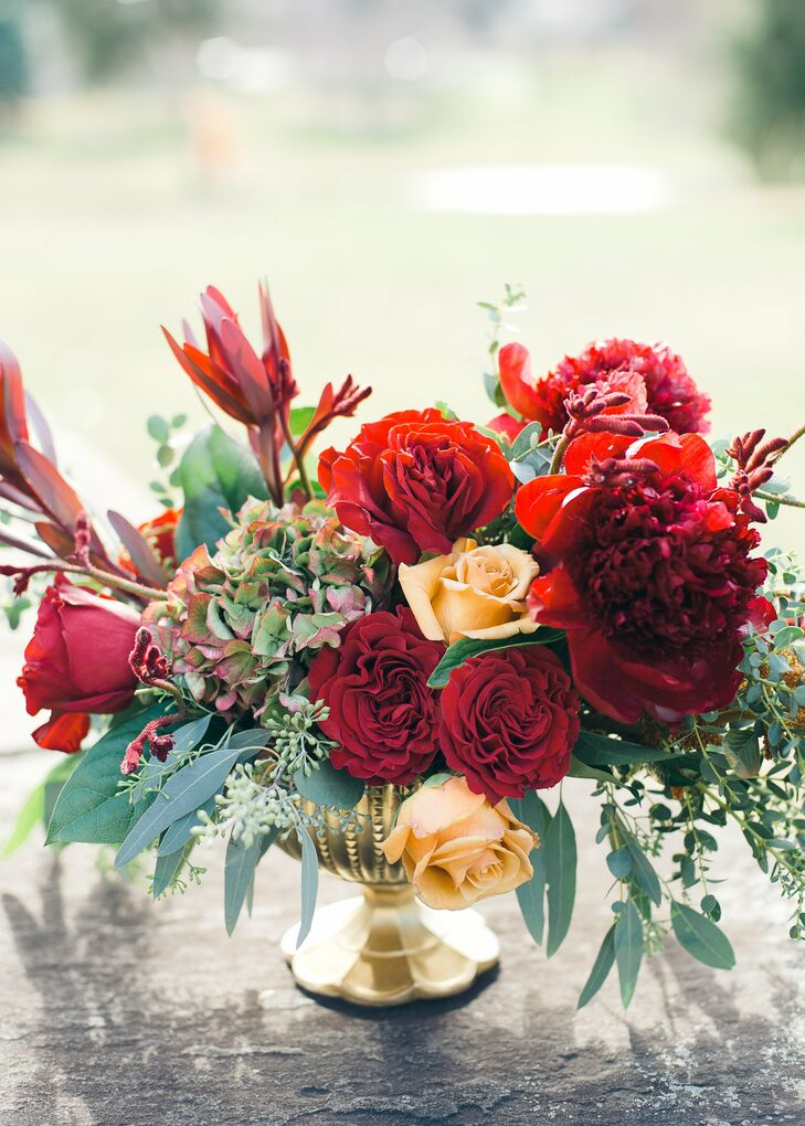 Red and pale orange roses accented with cascades of eucalyptus filled low gold vases for an elegant, autumnal look.