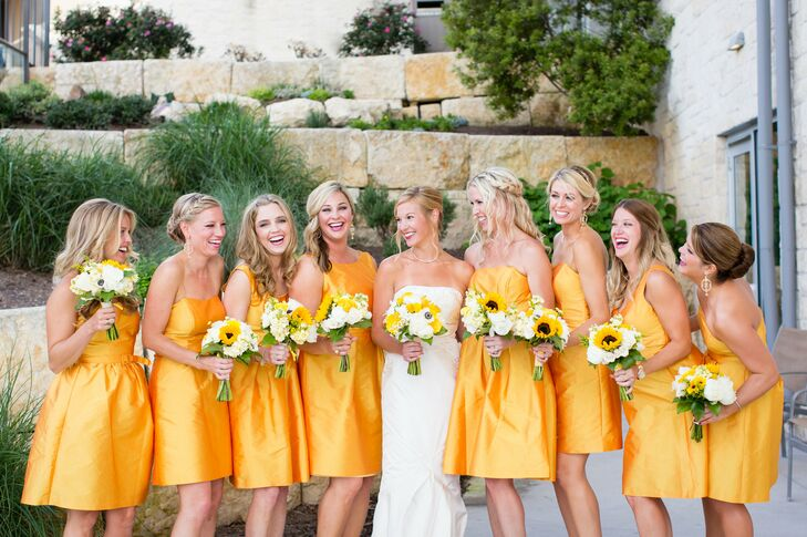 Claire's seven bridesmaids and maid-of-honor wore Alfred Sung dresses in different styles, but kept to the same cocktail-length for a cohesive look. They carried charming yellow and white bouquets of sunflowers, roses, stock and gerbera daisies.