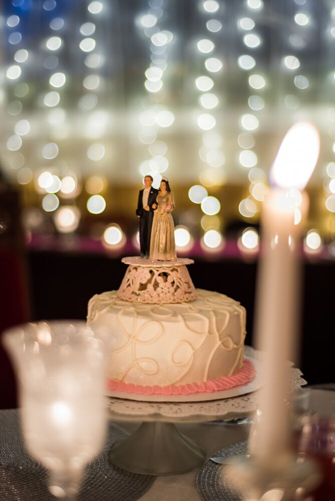 The ivory wedding cake was designed with a swirled pattern and had a ring of pink frosting around the bottom of the tier. The cake topper depicted a bride in a gold sparkly dress and a groom in a black tuxedo standing on a tall platform.