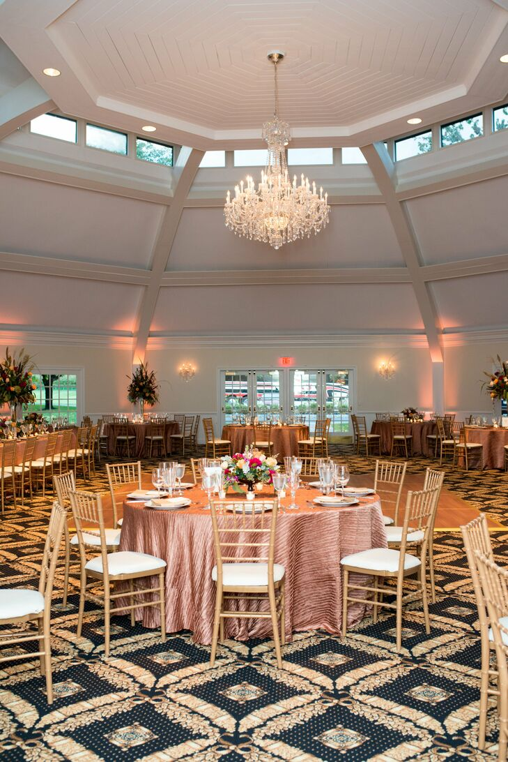 Dining tables at the winery ballroom were arranged with textured bronze linens and chiavari chairs. The dome-shaped hall features skylights and crystal chandeliers.