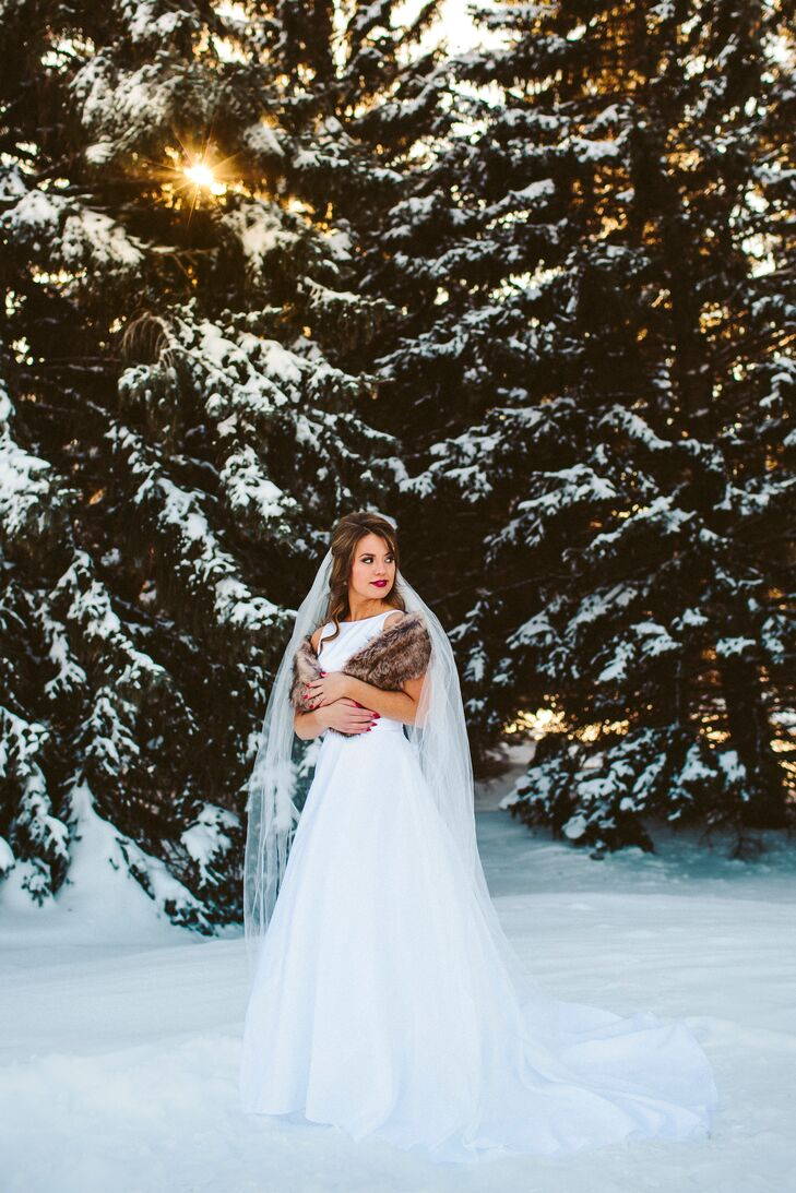 """Kelli chose a white satin gown from David's Bridal with a high Audrey Hepburn neckline tied at the waist with a white satin bow. """"I believe the dress is classic enough to be passed on to our future daughter(s) and or granddaughter(s),"""" says Kelli. rn"""
