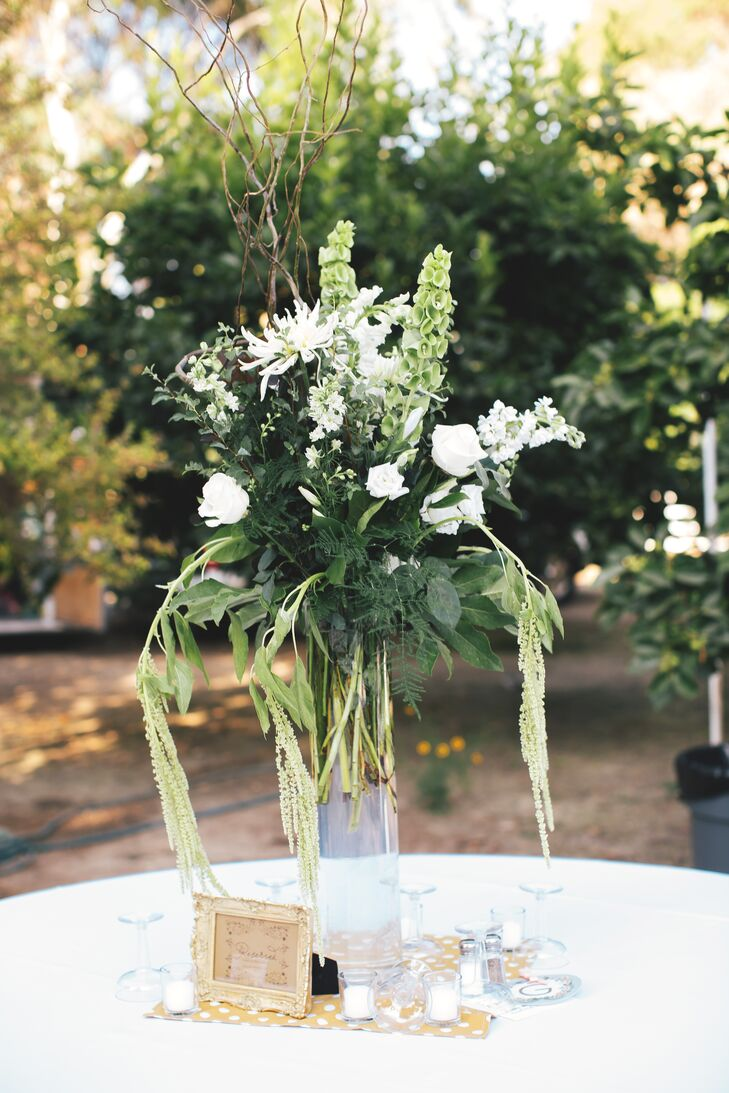 Lush arrangements or ivory roses and chrysanthemums mixed with bells of Ireland and white amaranths decorated dining tables at the reception.