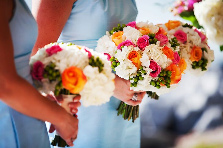 The bouquets were a colorful mix of orange and pink roses complemented by white hydrangea and green berries.