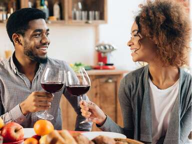 Couple toasting wine glasses containing red wine