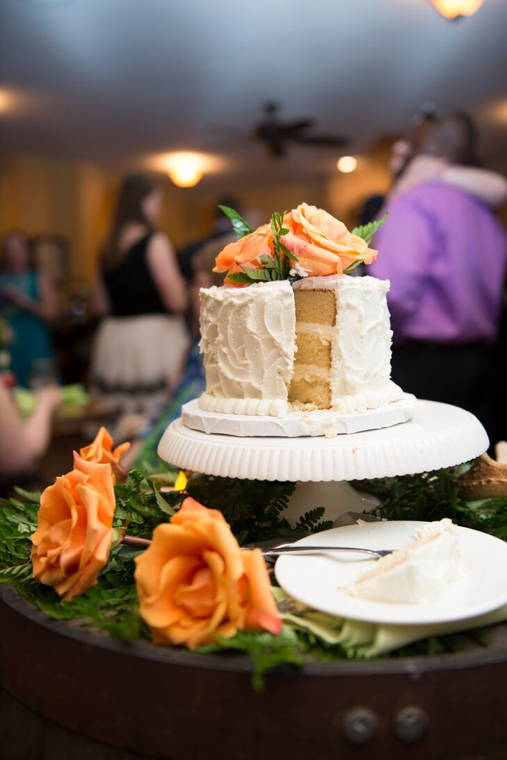 Cheryl and Travis had a simple buttercream wedding cake to cut at their wedding, which was decorated with orange roses.