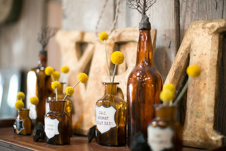 Playing up the venue's palette of gray, yellow and white hues, the couple wove bright blooms, like playful craspedias displayed in vintage bottles, throughout the room.