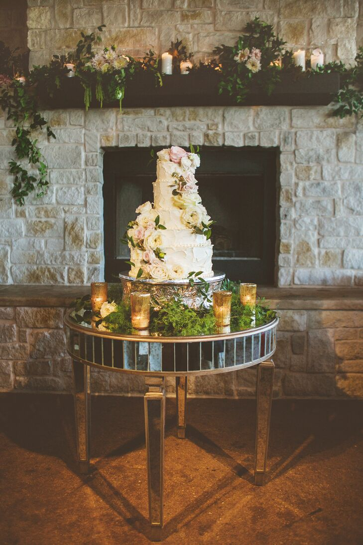 For their wedding cake, the couple chose two flavors which were alternated every other layer: raspberry almond torte and hazelnut mascarpone. The tiers were wrapped asymmetrically with real greenery and flowers to amplify the woodsy theme.