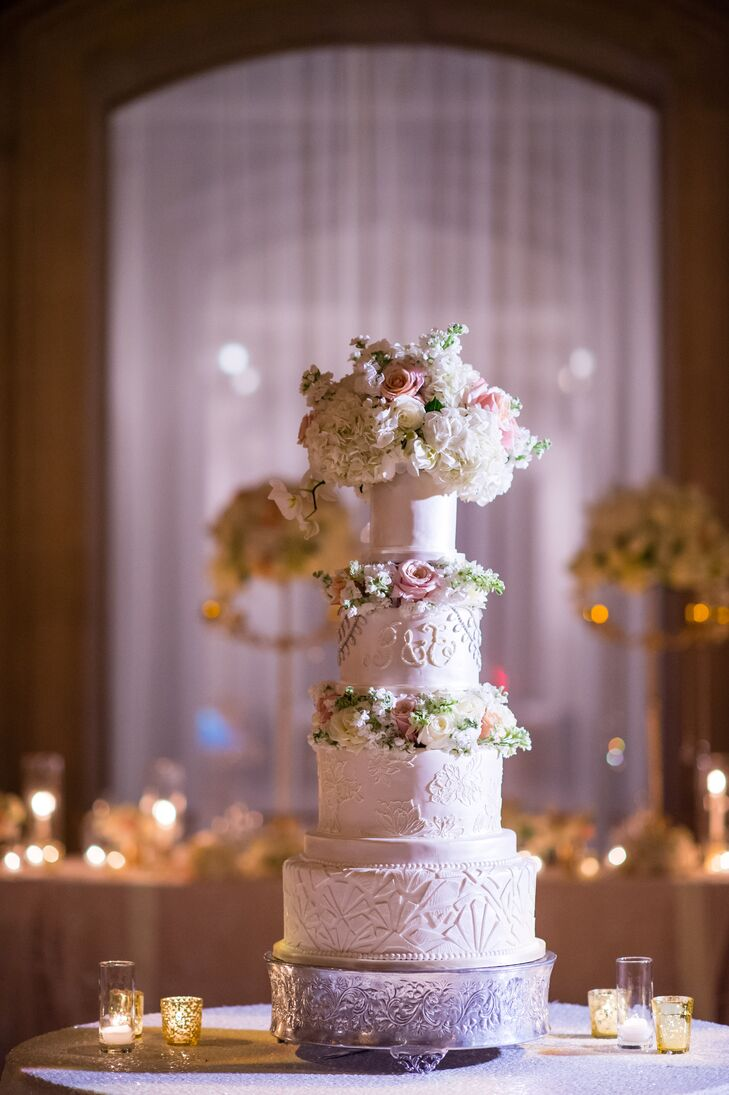 Beth's first-look wedding dress inspired the four-tier cake, with the bottom layer echoing her Galia Lahav gown and the top layer shimmering like her Zuhair Murad veil.