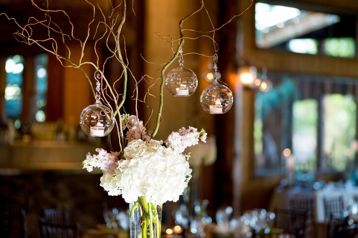 Dining tables were decorated with tall glass vase centerpieces, filled with ivory hydrangeas, pink stock and branches poking out on top. Glass orbs that contained tealights hung from the branches, adding a romantic glow.